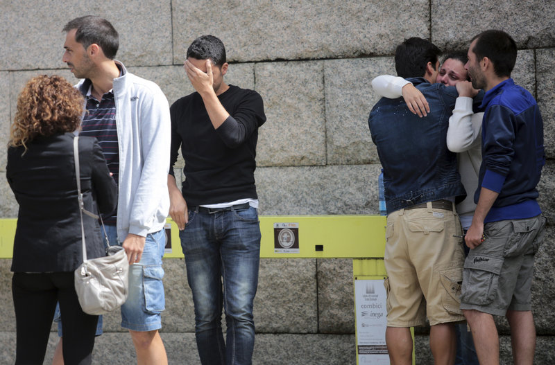 Relatives of a train crash victim comfort each other Thursday near Santiago de Compostela. More than 90 passengers were hospitalized, with 31 in critical condition.