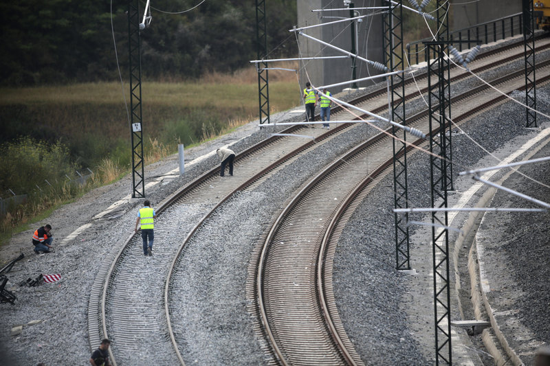 Workers stand on the track at the site of a fatal train crash in Santiago de Compostela, northwestern Spain, on Friday.