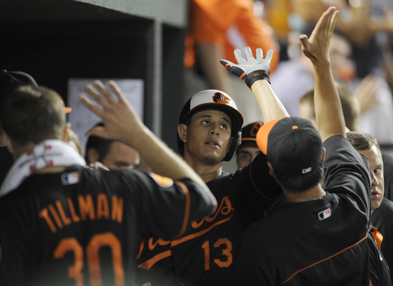 Manny Machado gets a big welcome from the dugout, including winning pitcher Chris Tillman, after homering for Baltimore in the seventh inning Friday night.