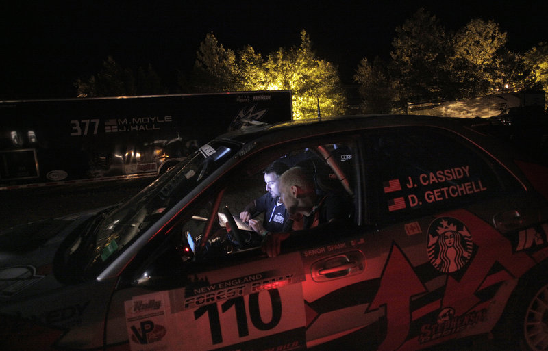 Erik Lee, in driver's seat, and Cullen Gillis sit in the front of Last Ditch Racing's Subaru rally car late Friday night as they go through final pre-race checks for the next day.