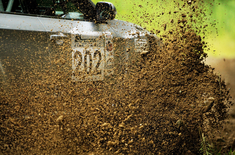 Dirt flies from a rally car as it navigates around a hairpin turn on the Newry race course.