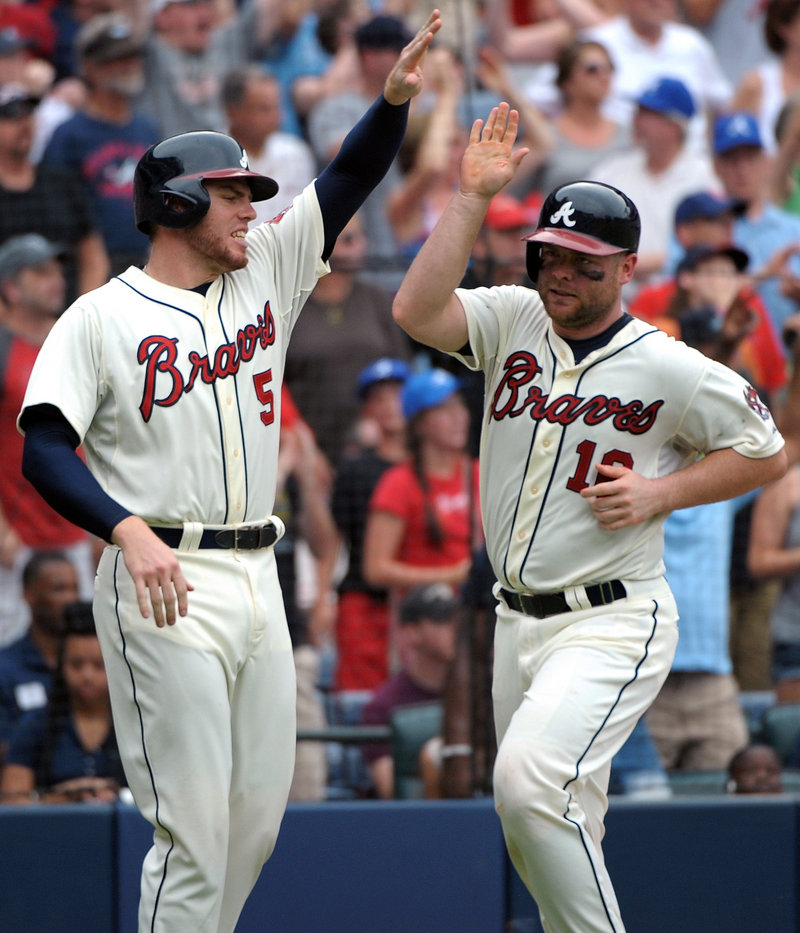 Freddie Freeman, left, greets Brian McCann after they scored on a double by Andrelton Simmons in the eighth inning to give Atlanta a 2-0 win over St. Louis.