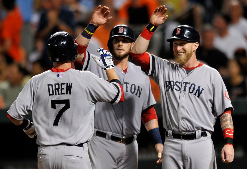 Stephen Drew is congratulated by teammates Jarrod Saltalamacchia, center, and Mike Carp after hitting a three-run homer Saturday night in the fourth inning of a 7-3 victory for the Boston Red Sox against the Baltimore Orioles.