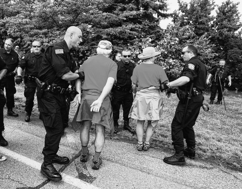 Anti-coal protesters are taken into custody as they set foot on the property of the Brayton Point Power Station in Somerset, Mass., Sunday.