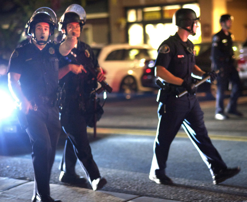 Police tell the crowd of onlookers to leave the area of a riot in Huntington Beach, Calif., Sunday.