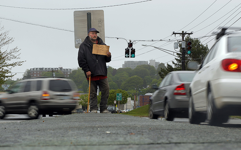 In this file photo, Don Dietz, 48, panhandles for change in the median at the corner of Franklin Street and Marginal Way in Portland on Friday, May 24, 2013.