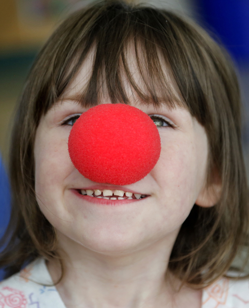 Kaitlyn Frost, 4, of Waterville tries on a clown nose as members of Circus Smirkus Big Top Tour make a stop at The Barbara Bush Children's Hospital at Maine Medical Center on Sunday.