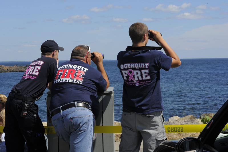 Tom Cryer, Gus Dunham and Jordan Moore of the Ogunquit Fire Department watch from shore Friday as searchers work the waters of Perkins Cove looking for a local fishermen who went missing Thursday night from a boat. Search2