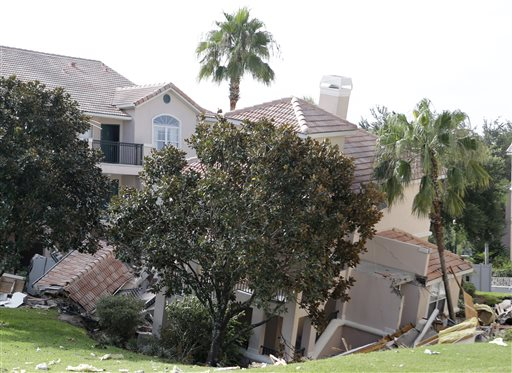 A portion of a building rests in a sinkhole Monday in Clermont, Fla. The sinkhole, 40 to 50 feet in diameter, opened up overnight and damaged three buildings at the Summer Bay Resort.