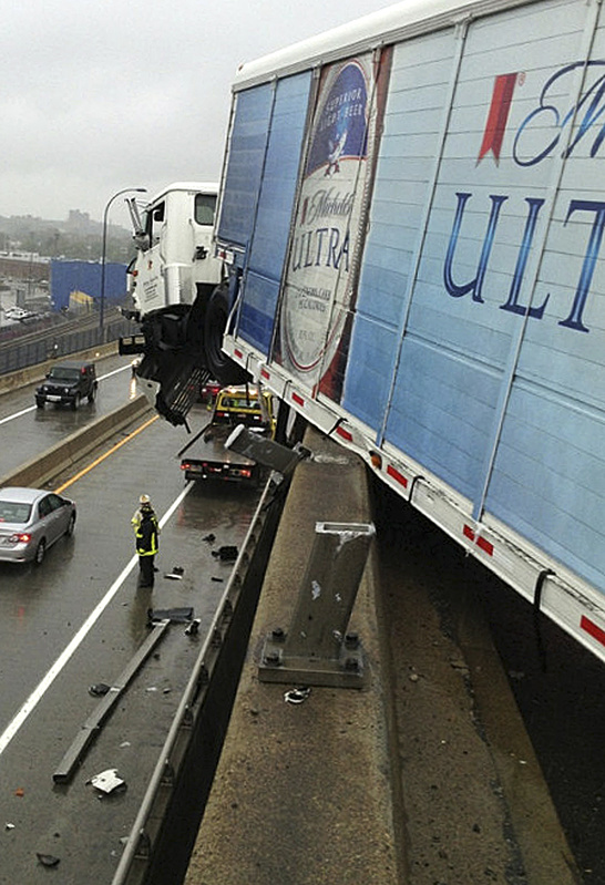 A beer delivery truck hangs off Interstate 93 over the Leverett Connector highway ramp after striking a guardrail Friday in Boston.