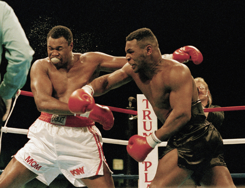 Mike Tyson, right, follows through on a punch to Larry Holmes during a heavyweight title boxing fight in Atlantic City, N.J., in 1988. Tyson now is a promoter. Boxer,Boxing,Punching,Ring,Rope,Strength,Violence