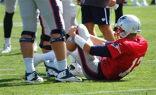 Quarterback Tom Brady grabs his left knee after an apparent injury Wednesday during a joint workout with the Tampa Bay Buccaneers at training camp in Foxborough, Mass.
