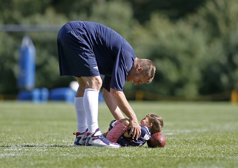 New England Patriots quarterback Tom Brady plays with his son Benjamin Thursday following the Patriots' joint workout with the Tampa Bay Buccaneers at NFL football training camp in Foxborough, Mass.