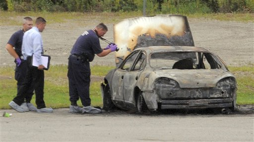 Police investigate a vehicle that burned before dawn Monday, Aug. 13, 2012, off Target Industrial Circle in Bangor, Maine. After the fire was extinguished, three bodies were found inside the parked car. One of two southern New England men charged with killing three Maine residents last year and then setting fire to a car containing the bodies told investigators that one victim pleaded for her life before being shot. (AP Photo/Bangor Daily News, Gabor Degre)