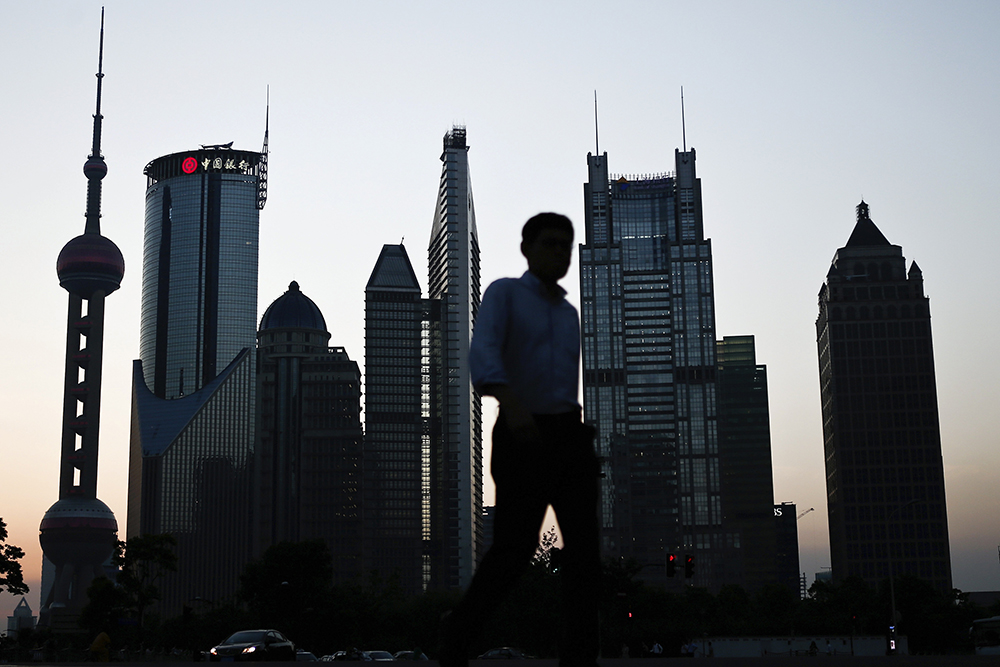 In this photo taken July 10, 2013, a man walks past the downtown skyline of Shanghai, China. China's consumer inflation held steady in July and a fall in producer prices decelerated in a new sign a slump in the world's second-largest economy might be stabilizing. (AP Photo)