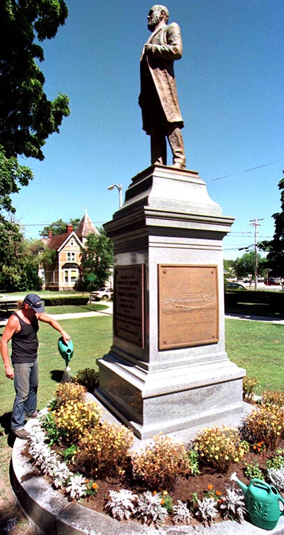A parks department worker waters flowers at the base of the Thomas Goodall statue in Sanford's Central Park in this 1997 file photo.