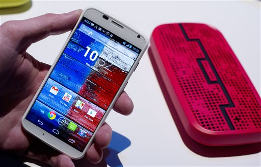 The Motorola Moto X smartphone uses Google's Android software. In the background is a Deck, from Sol Republic, which is a wireless speaker that operates up to 300 feet from the phone using Bluetooth technology.