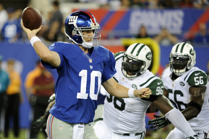 New York Giants quarterback Eli Manning (10) throws a pass away from New York Jets defensive end Muhammad Wilkerson (96) and Ricky Sapp (55) during the first half of a preseason NFL football game, Saturday, Aug. 24, 2013, in East Rutherford, N.J. (AP Photo/Bill Kostroun)