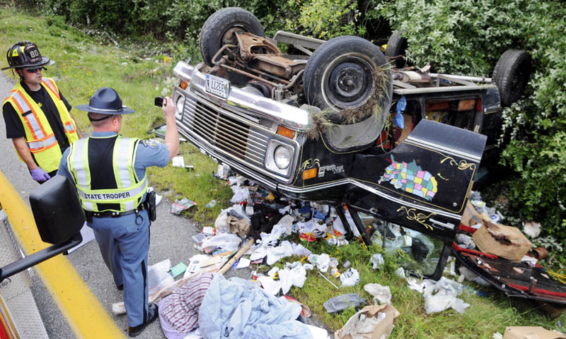 Maine State Trooper Dane Wing photographs a van with Augusta firefighter/paramedic Sean Estabrook on Tuesday Aug. 13, 2013. An I-95 crash killed the occupant after the van rolled over on the offramp for exit 112A in Augusta.