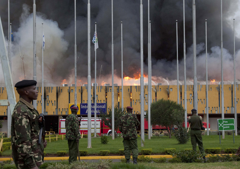 Police stand guard as fire engulfs the international arrivals area of Jomo Kenyatta International Airport in Nairobi, Kenya, on Wednesday.