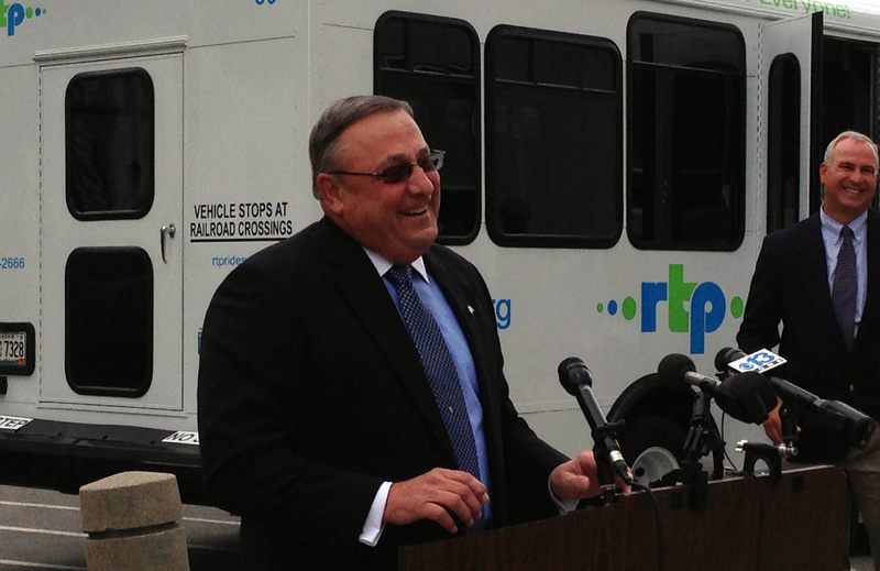 Gov. Paul LePage announces the launch of a bus refurbishing program designed to extend the life of regional transit buses run by nonprofit agencies. At right is Tim Corbett, executive director of the Maine Military Authority, which is doing the overhauls. A refurbished bus run by the Portland-based Regional Transportation Program is at rear.
