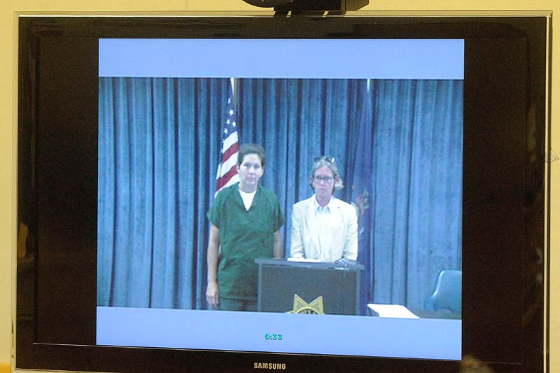 BethMarie Retamozzo, left, stands with Lisa Whittier, attorney representation for her arraignment via video conference with Judge Charles Dow. at the Waterville District Court on Wednesday.