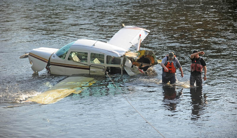 Charles Robins, left, of Charlie and Sons garage and Chad Robertson, right, with the Maine Warden Service, prepare to haul a single-engine Beechcraft airplane from the Kennebec River today, after it crashed on take-off from Gadabout Gaddis Airport in Bingham. The aircraft was piloted by Ray Ayer, 59, of Monmouth, and had one passenger, Paul Householder, 54, of Wayne. No injuries were reported.