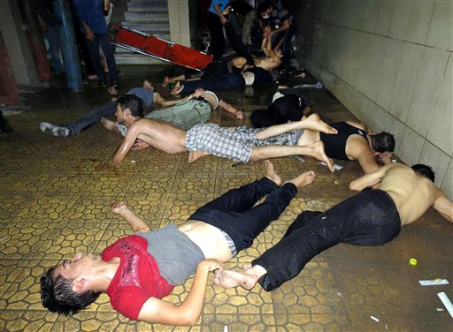 This citizen journalism image provided by the Media Office Of Douma City shows Syrian men lying on the ground as they wait for treatment after an alleged poisonous gas attack fired by regime forces. The photo was authenticated based on its contents and other AP reporting.