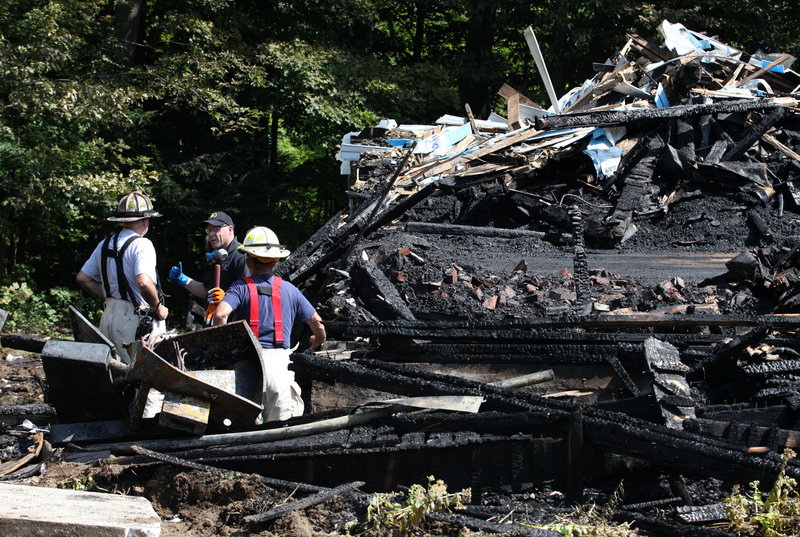 North Yarmouth Fire Chief Ricky Plummer, left, and Deputy Fire Chief Harold Stoddard, right, speak with State Fire Marshal Senior Chief Investigator Chris Stanford, center, looks through the remains of the Wescustogo Grange Hall that was destroyed by fire Friday, Aug. 30, 2013 in North Yarmouth.