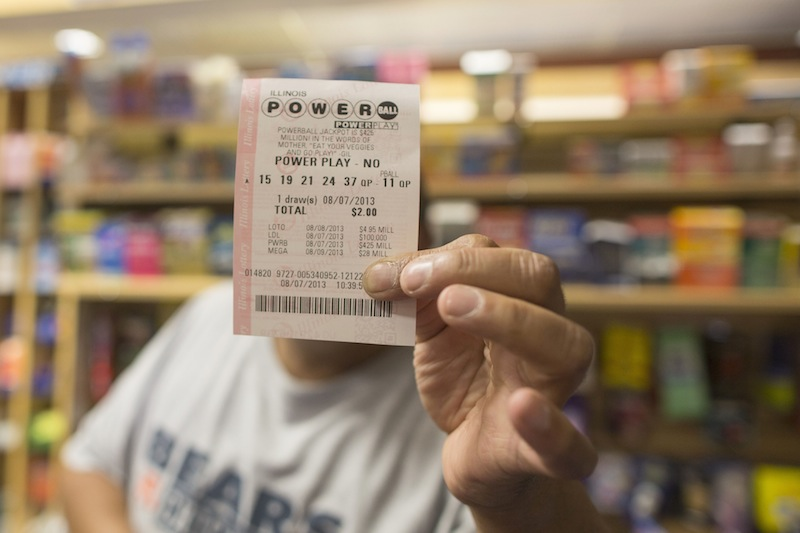 A man holds up his Powerball ticket inside of a convenience store in Chicago on Wednesday.