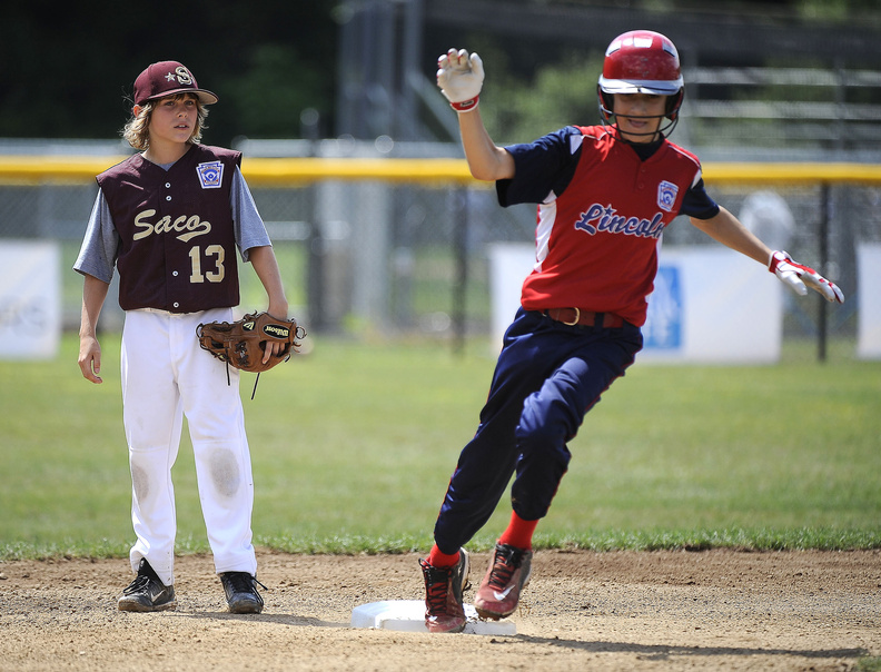 Aaron DeSouza of Lincoln, R.I., rounds second base and heads toward third as Saco's Timmy Smith looks on during Lincoln's 11-2 win Friday at the Little League New England Regional.