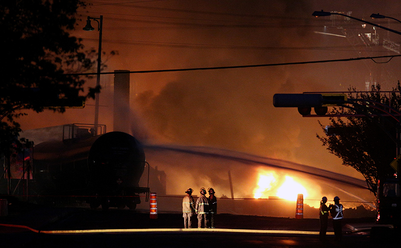 Firefighters look at a train wagon on fire at Lac Megantic, Quebec, July 6, 2013 after a runaway oil train crashed and caused numerous explosions. 47 people died and much of the Quebec town was destroyed. The company faces over $200 million in crash claims but only has a $25 million policy.(REUTERS/Mathieu Belanger)