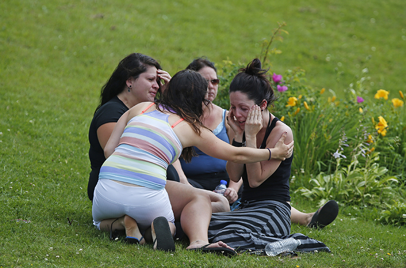 A woman comforts her friend while they sit on the grass at the Polyvalente Montignac, the school sheltering the people who were forced to leave their houses after the explosion, in Lac Megantic, July 7, 2013. Nearly 50 people died in the crash and 30 buildings were destroyed. (REUTERS/Mathieu Belanger) :rel:d:bm:GF2E9771BAG01