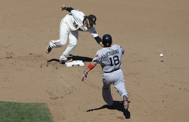 San Francisco Giants shortstop Brandon Crawford cannot catch the ball after a throwing error by San Francisco Giants pitcher Michael Kickham as Boston Red Sox's Shane Victorino (18) runs toward second base during the eighth inning in San Francisco on Wednesday.