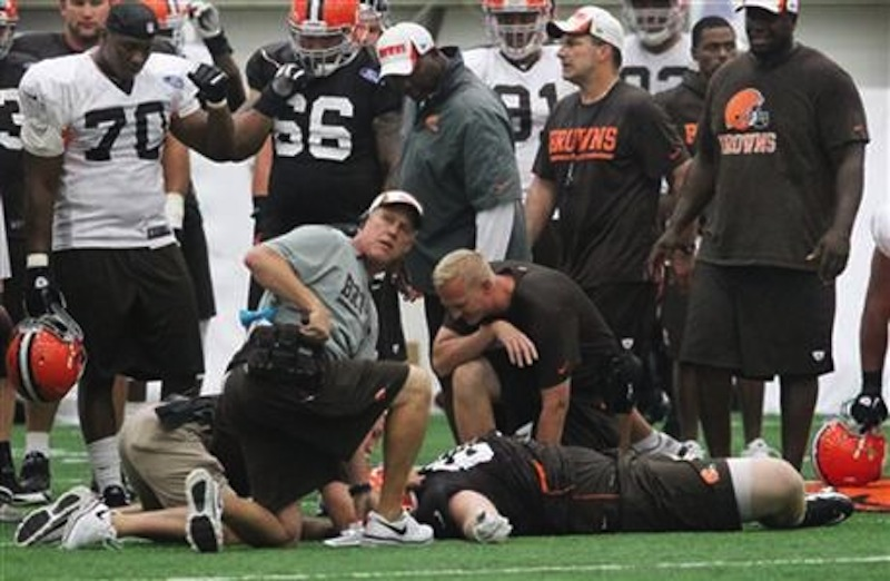 Cleveland Browns offensive lineman Ryan Miller is attended to by the team's medical staff after he suffered a concussion during NFL football training camp Saturday, July 27, 2013, in Berea, Ohio. (AP Photo/The Plain Dealer, John Kuntz)