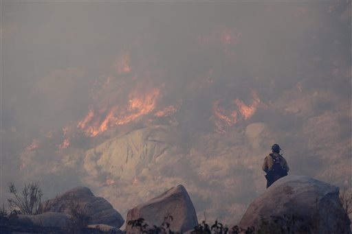 A firefighter watches a backfire burn while battling a wildfire in Banning, Calif.
