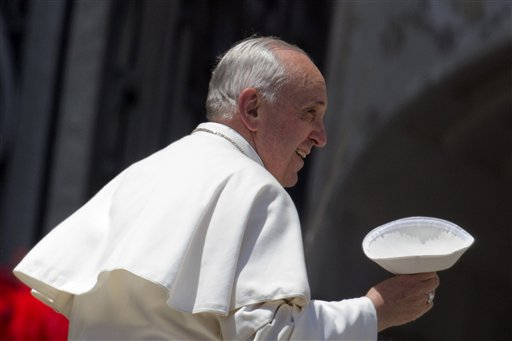 Pope Francis holds his skull-cap as he leaves at the end of his weekly general audience in St. Peter's Square, at the Vatican, in this May 29, 2013, photo.