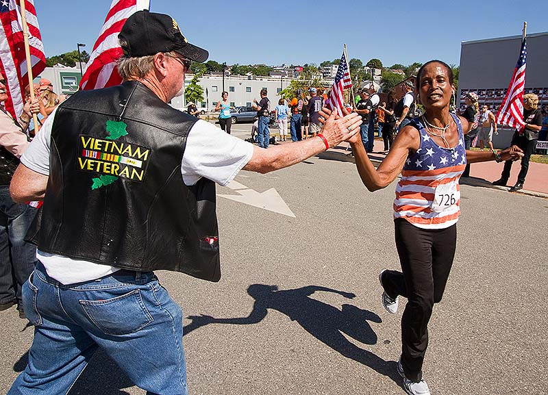 Vietnam veteran Jim Merrill of Auburn gives a high-five to a finisher of the sixth annual Run for the Fallen Maine in Portland on Sunday.