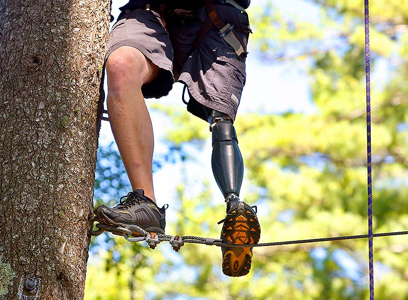 Roy Mitchell, of the Army's 10th Mountain Division, maneuvers through the ropes course Saturday during Maine Adaptive Sports & Recreation's ninth annual Veterans No Boundaries summer program at Camp Wavus on Damariscotta Lake in Jefferson.