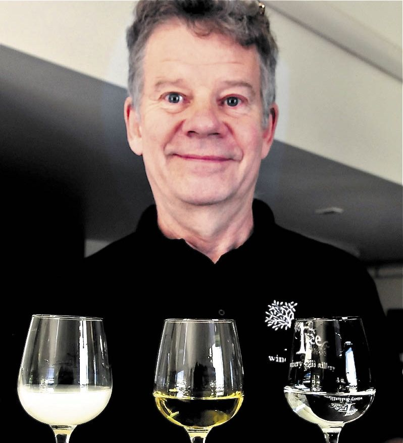 Bruce Olson, co-owner of Tree Spirit Winery, holds a tray of absinthe in different stages of production at the Oakland company. At left is a glass of absinthe in the Louche phase, a more flavorful version that turns white after water is added. The center glass is the finished version that is more potent, with a green tint from added herbs. At right is the clear, beginning phase.