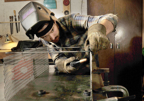 Metal fabricator John Nelson welds a basket at his Portland shop.