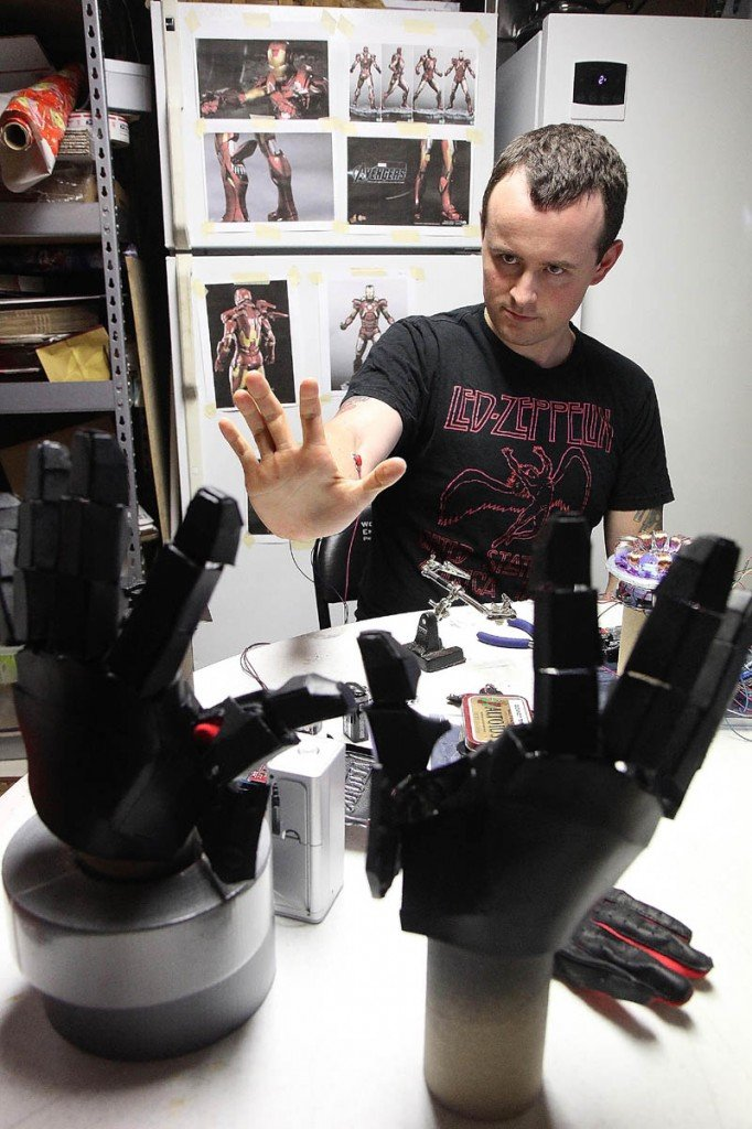 Thomas Lemieux tests a bionic repulsor, which activates the hands on his life-size Iron Man costume, in the basement of his Oakland home recently.
