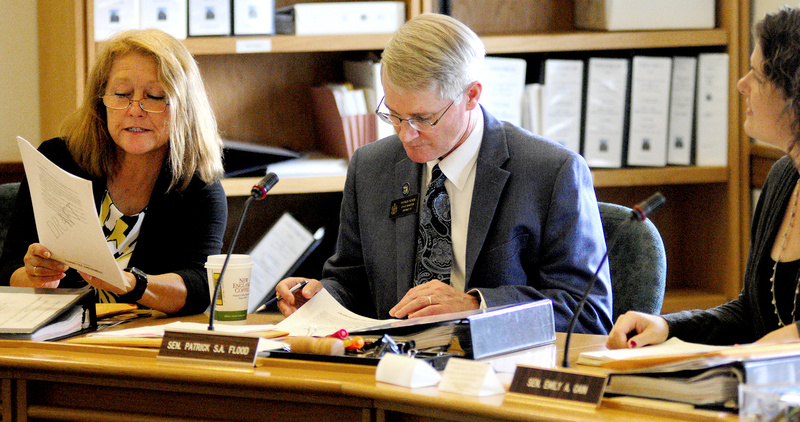 Rep. Kathleen Chase, R-Wells, Sen. Patrick Flood, R-Winthrop, and Sen. Emily Cain, D-Orono, confer over a draft version of L.D. 1515 before a work session of the Appropriations and Financial Affairs committee Thursday at the State House in Augusta.