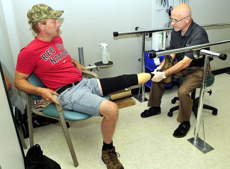 Prosthetist Kevin Carroll, right, evaluates the prosthetic device worn by Ronald McLaggan, of South China, at the Hanger Clinic in Waterville on Thursday.