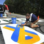 "Matt Tobin and Jeremy Gardner paint the starting line area on Route 77 in Cape Elizabeth on Wednesday morning in preparation for Saturday's Beach to Beacon road race. The ""Boston Strong"" ribbon is an addition this year to support the city and the marathon bombing victims."