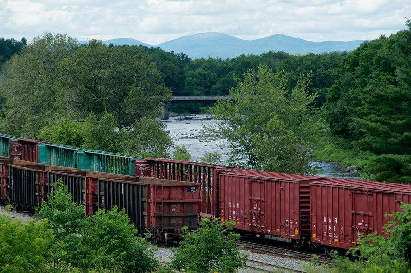 "Boxcars owned by the Montreal, Maine & Atlantic Railway sit idle next to the Pleasant River in Brownville last Tuesday. The cars still carry the ""BAR"" markings of the Bangor and Aroostook Railroad, which operated between 1891 and 1995. A significant part of the company's business was hauling potatoes from Aroostook County in heated boxcars."