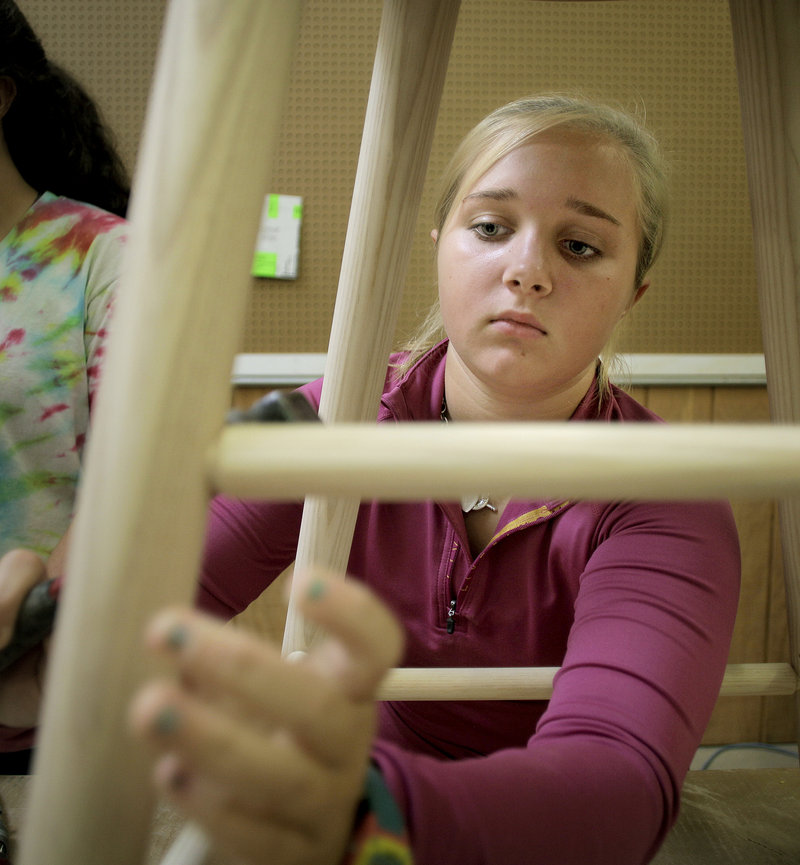 Kate Spade of St. Timothy's all-girls private school in Maryland fixes a peg into a stool at the Thos. Moser Cabinetmakers Workshop in Auburn, Maine on Thursday, August 1, 2013. The girls were in Auburn all week making furniture for their new student center.
