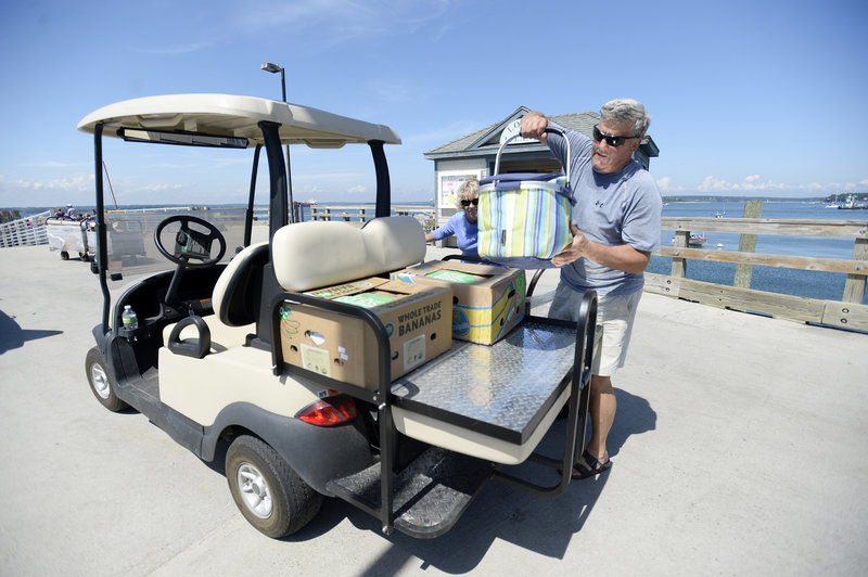 Wes Wolfertz of Long Island loads up his golf cart after making a trip to the mainland for supplies Thursday, August 1, 2013