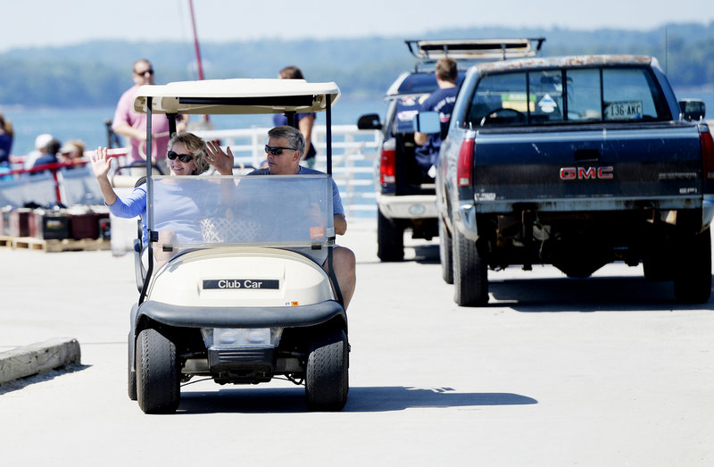 Camille and Wes Wolfertz of Long Island wave as they drive their golf cart away from the Long Island dock after a trip to the mainland for supplies Thursday, August 1, 2013.