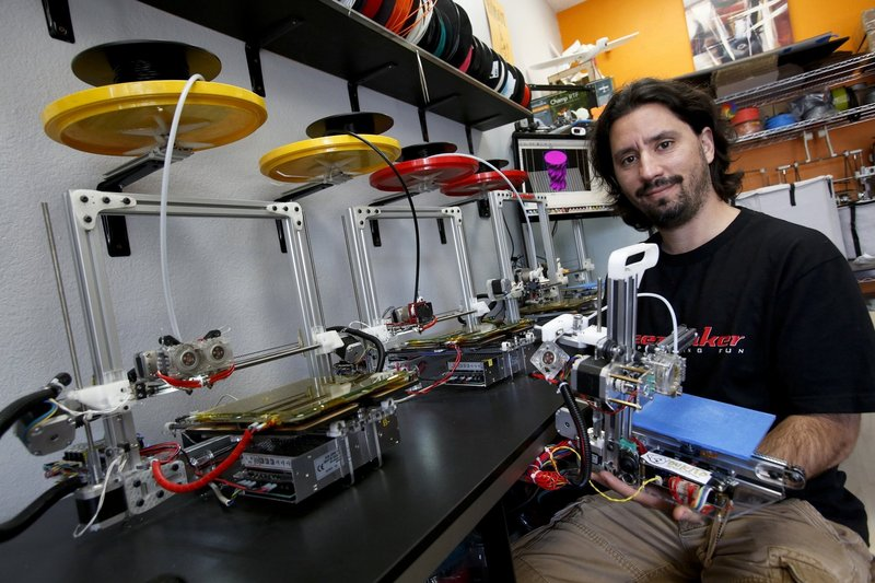 Diego Porqueras holds a Bukito 3-D printer. Bukobot 3-D printers sit on the counter.